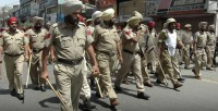 Police stride through streets in Punjab after Sikh religious summit.